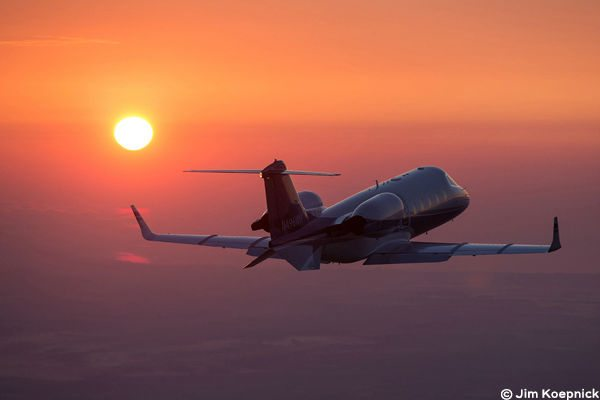 A Learjet flying at dawn